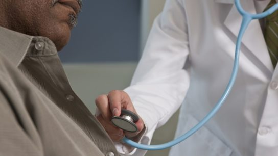 Doctor checking black man's heart with stethoscope