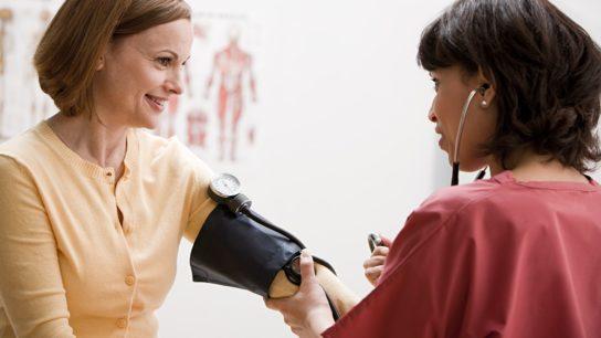 Nurse taking female patient's blood pressure.