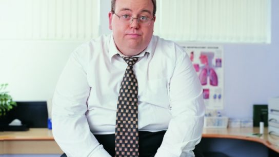 Obese man sitting in doctor's office