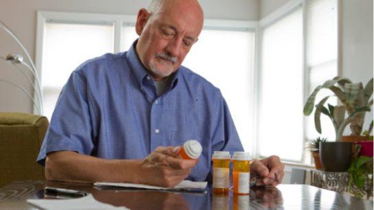 Sad senior man taking pills