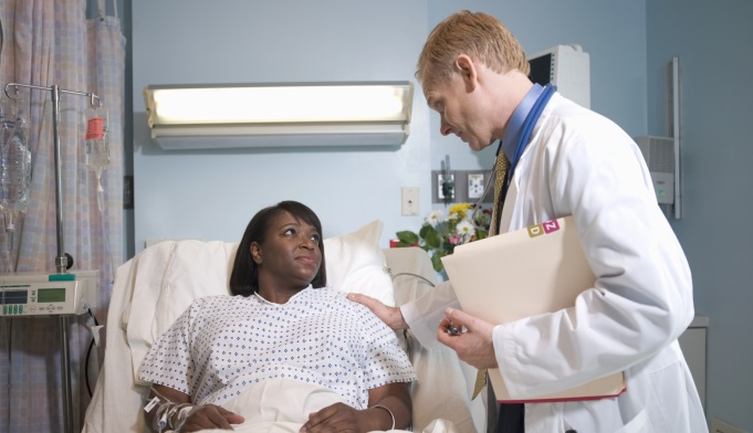 Doctor visiting black woman in hospital room