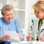 Senior woman showing paper to doctor
