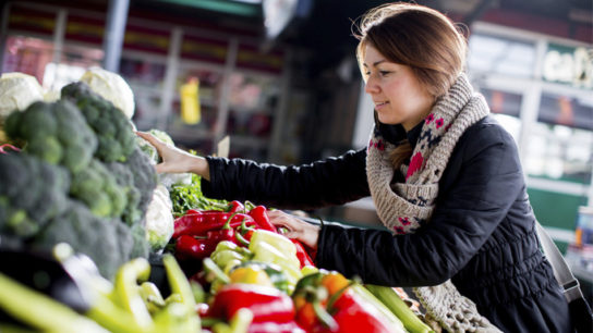 A young woman buys vegetables from the farmer's market