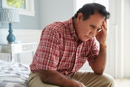 Worried older man sitting on bed