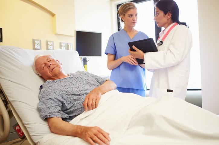 Senior man eyes closed in hospital bed