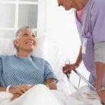 Happy hospital patient talking to nurse