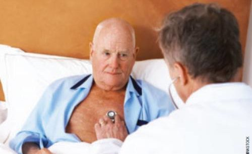 Doctor checking man's heart with stethoscope