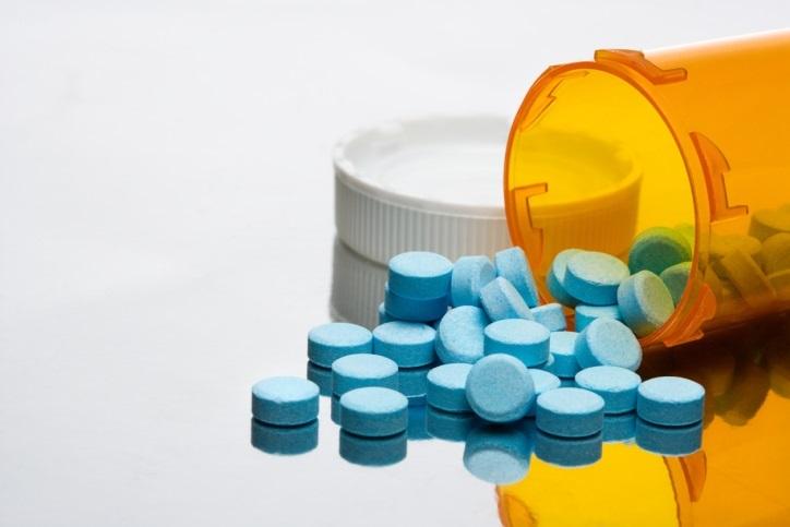 Blue pills spilling from bottle