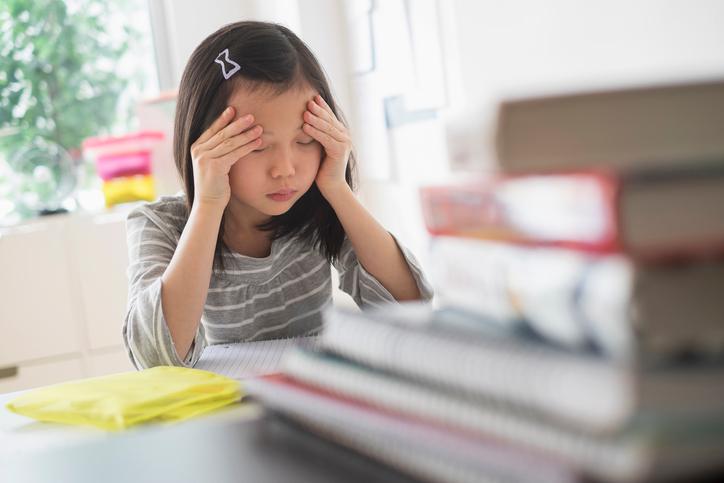 anxious girl rubbing forehead doing homework