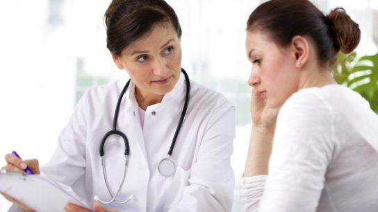 Doctor talking to young woman