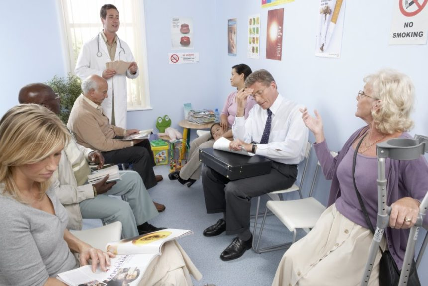 Full waiting room with patients and a doctor