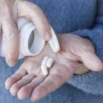 Older person taking pills, closeup of hands