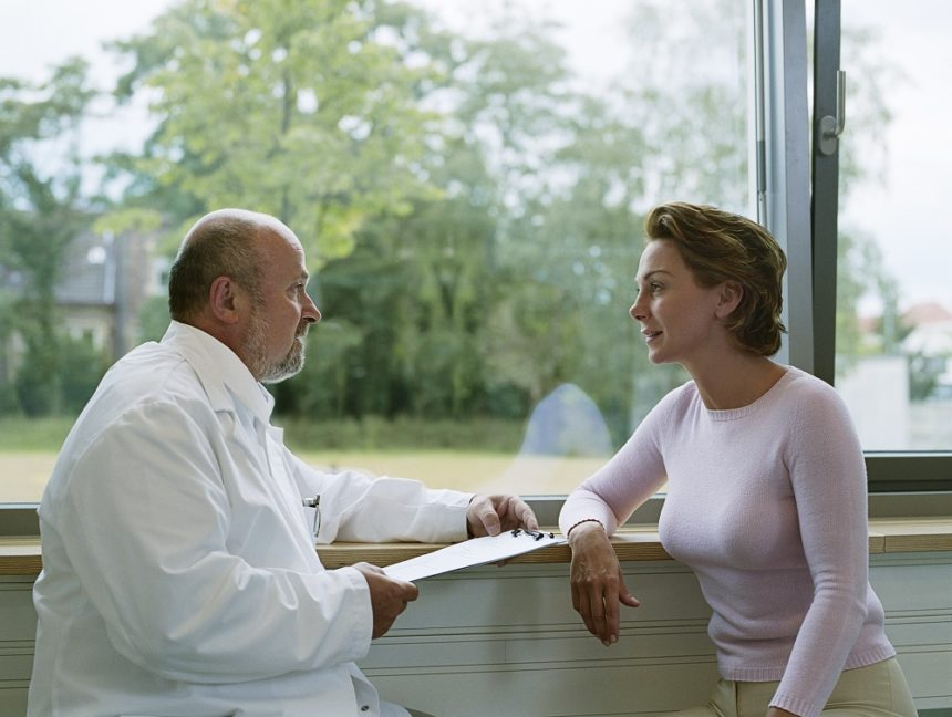 doctor talking to patient near window
