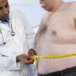 Obese man being measured by a doctor