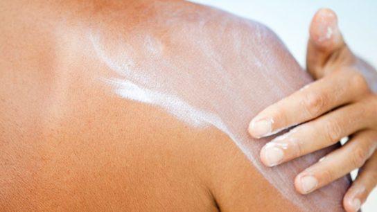 A woman applying sunscreen lotion