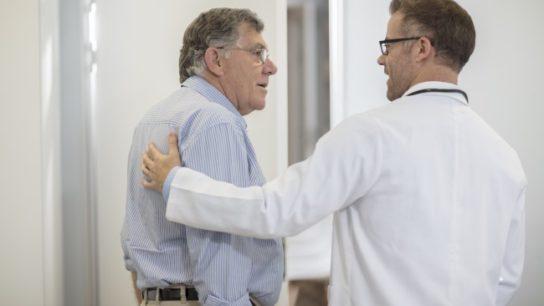 Doctor escorting senior man down the hall