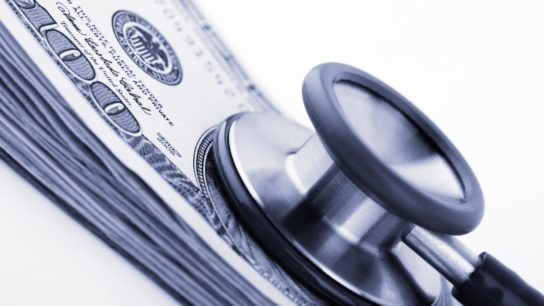 Stethoscope on stack of one hundred dollar bills