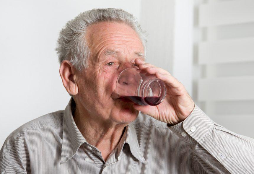 man drinking dark purple drink
