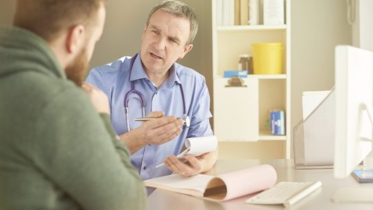 doctor has serious talk with young male patient