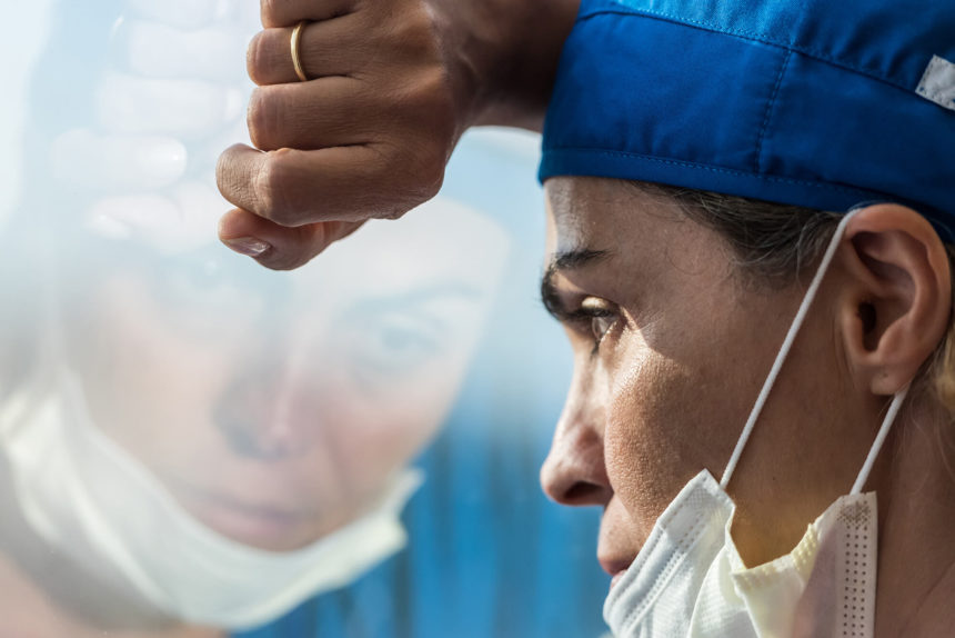 Overworked healthcare worker looking through a window.