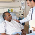 Doctor visiting Black man in hospital bed