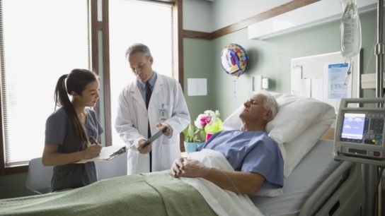 A doctor and nurse making rounds in a hospital room.