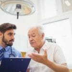 An elderly patient speaks with a doctor.